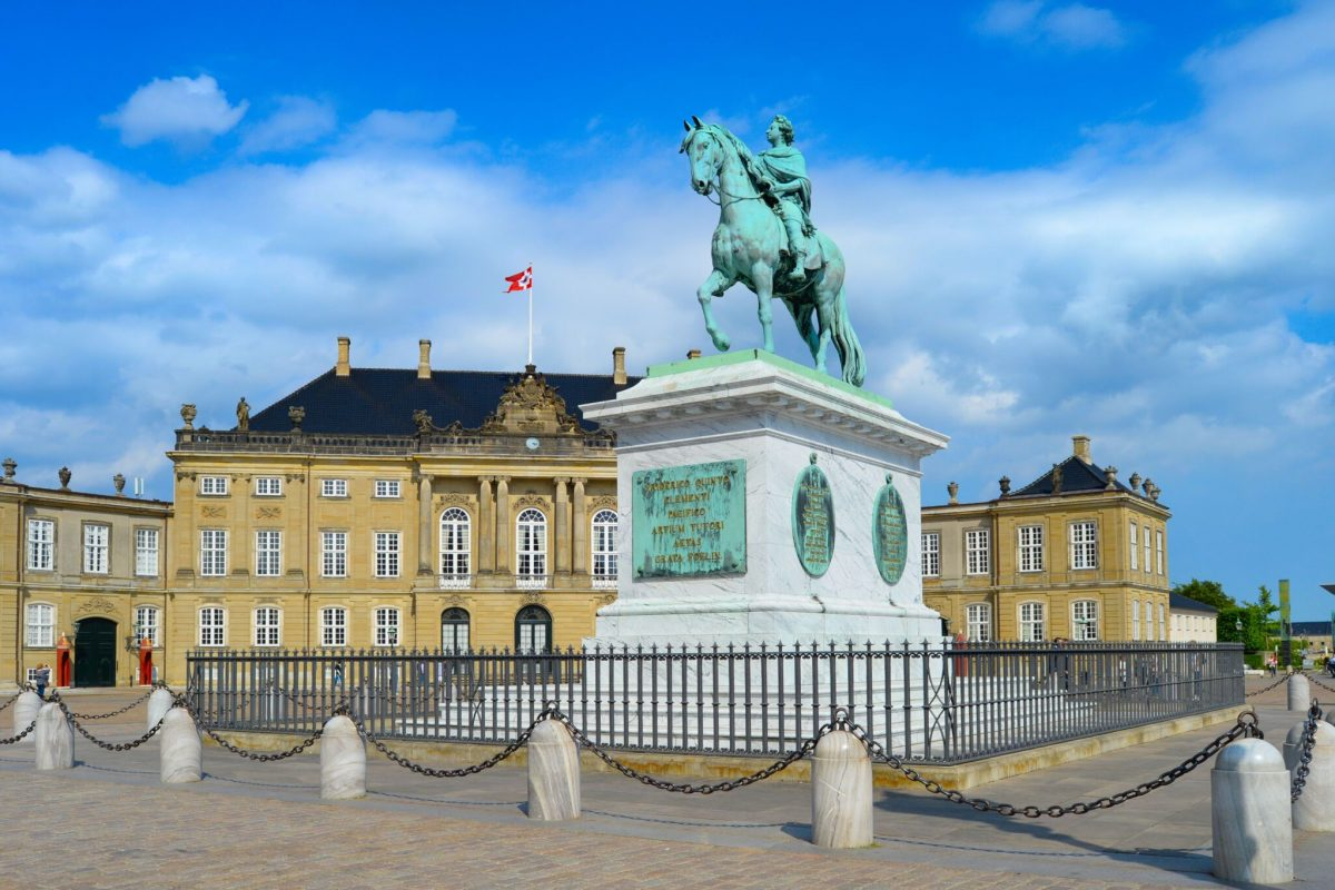 Equestrian statue of Frederik V by Amalienborg courtyard architectural building in sunny day, Copenhagen, Denmark